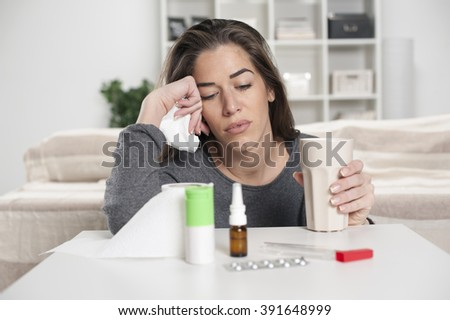Girl who is not feeling well sits and looks at drugs on the table - stock photo