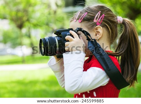 Girl who takes pictures with a photo camera in park - stock photo