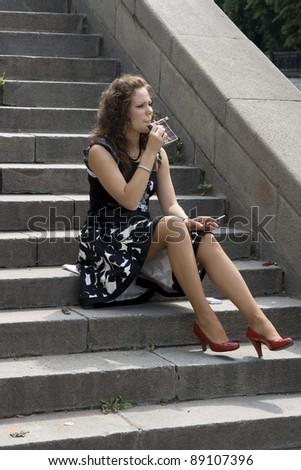 Girl with a a cigarette sitting on step