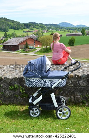Girl with a baby stroller enjoing Alpine panorama. Switzerland - stock photo