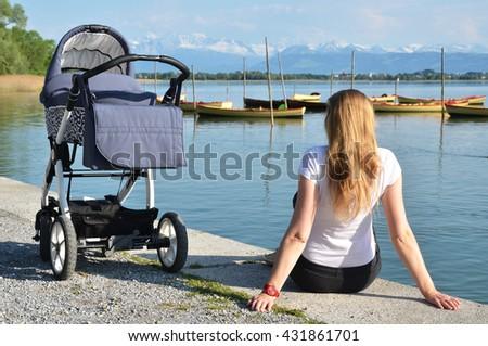 Girl with a baby stroller enjoying Alpine panorama. Switzerland - stock photo