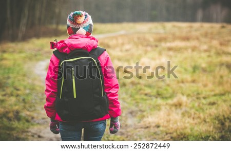 girl with a backpack going up the path - stock photo