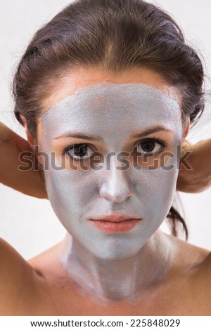 Girl with a beautician at spa salon. Beautician performs cosmetic procedures.applying cosmetic mask by brush. Cosmetology, facial, beauty - The concept of facial skin care.