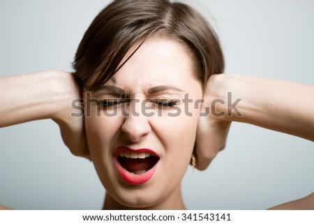 girl with a beautiful face closes his ears, bright photo lifestyle, photo studio on isolated gray background - stock photo