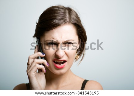 girl with a beautiful face upset talking on the phone, bright photo lifestyle, photo studio on isolated gray background - stock photo