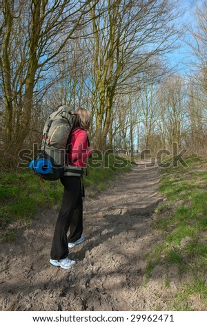 Girl with a big backpack walking in a forest. - stock photo