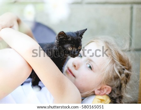 girl with a black kitten playing / lying on the couch
