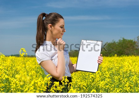 girl with a blank paper file on yellow flower field - stock photo