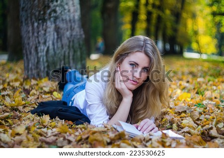Girl with a book in an autumn park