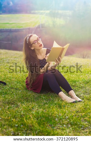 Girl with a book in nature