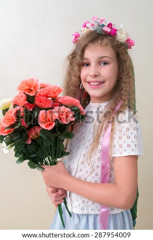 Girl with a bouquet of artificial flowers in hands and wreath on her head - stock photo
