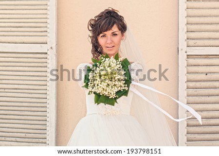Girl with a bouquet of flowers standing at the wall