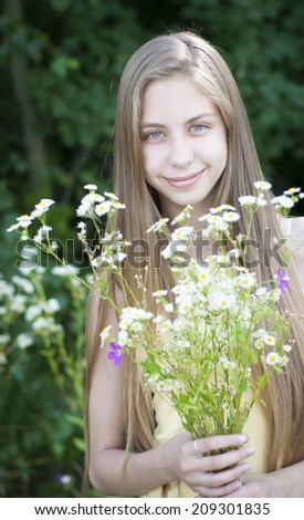 Girl  with a bouquet of wild  flowers - stock photo