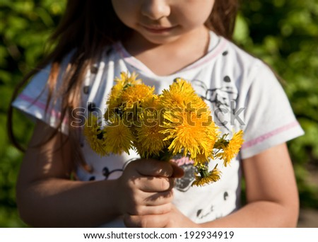 Girl with a bouquet of yellow dandelions - stock photo