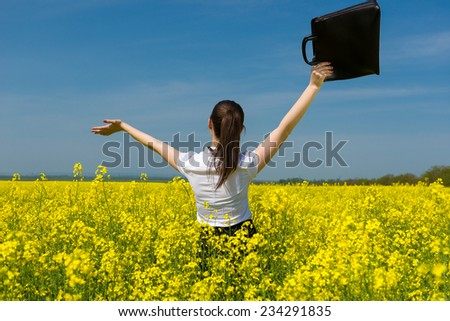 girl with a briefcase on yellow flower field - stock photo