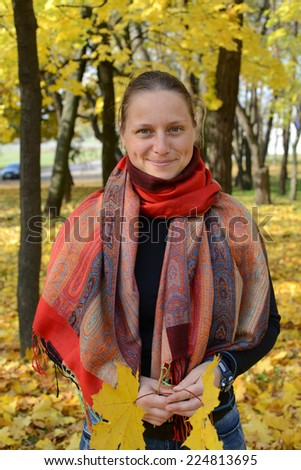 Girl with a bright scarf in autumn park - stock photo