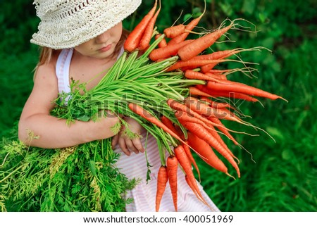 Girl with a bunch of freshly clean carrots - stock photo