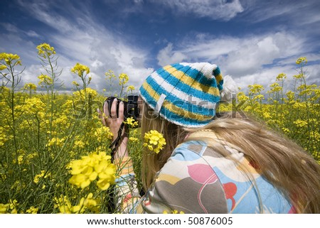 girl with a camera on a background of yellow flowers - stock photo