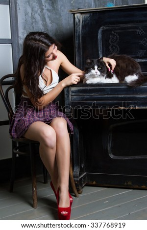 girl with a cat sitting at the piano - stock photo