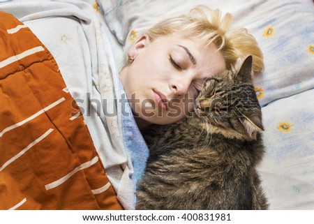 girl with a cat sleeping in bed - stock photo