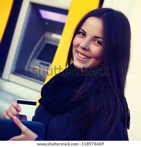 girl with a credit card at an ATM - stock photo