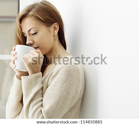 Girl with a cup in profile at the window - stock photo