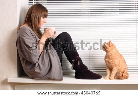 Girl with a cup of cappuccino and a cat at the window - stock photo