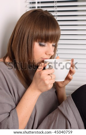 girl with a cup of cappuccino at the window - stock photo