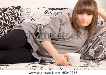 Girl with a cup of cappuccino on a sofa - stock photo
