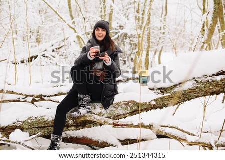 Girl with a cup of tea sitting on a tree in winter