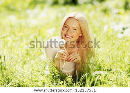 girl with a dandelion in his hand lying on the grass - stock photo