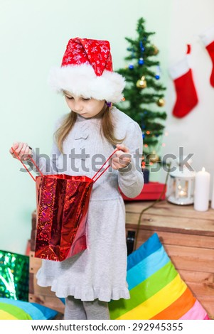 Girl with a disappointed face looking into the bag with Christmas present - stock photo