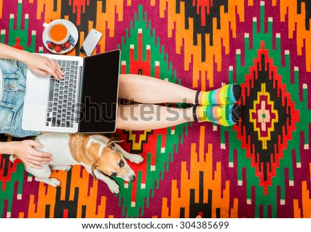 girl with a dog at the computer sitting on the floor with a cup of herbal tea. Beautiful national rug home comfortable relaxed atmosphere. Top view. Beautiful fit slim legs - stock photo