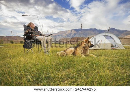 Girl with a dog in the tourism campaign on vacation - stock photo