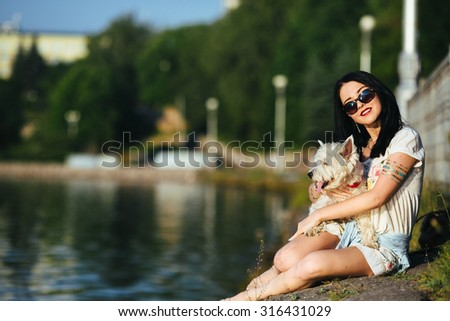girl with a dog on the shore looking at the lake - stock photo