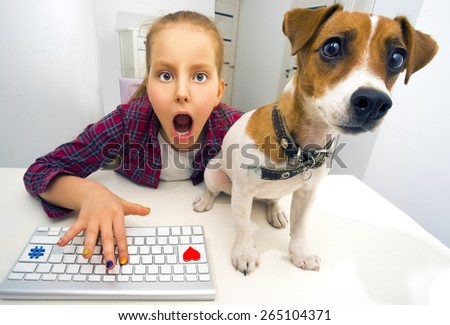 Girl with a dog watching a computer monitor. They have an unusual keyboard. - stock photo