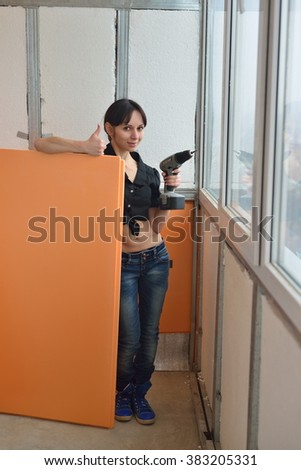 Girl with a drill secures insulation on the balcony - stock photo