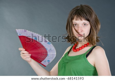 girl with a fan on a black background - stock photo