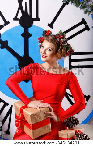 Girl with a gift and a hairstyle sitting next to a big clock. Five to midnight. Christmas Eve. New Year. Waiting for a miracle. Merry Christmas. 2017 - stock photo