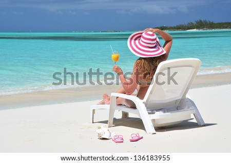 Girl with a glass of orange juice on the beach of Exuma, Bahamas - stock photo