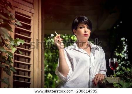 Girl with a glass of red wine and a cigarette Beautiful young girl with a glass of red wine and a cigarette - a break - stock photo