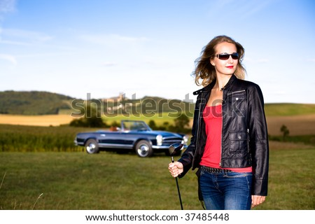 Girl with a Golf Driver and Post-War classic car - stock photo