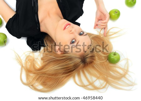 Girl with a green apple lies on the isolated background - stock photo