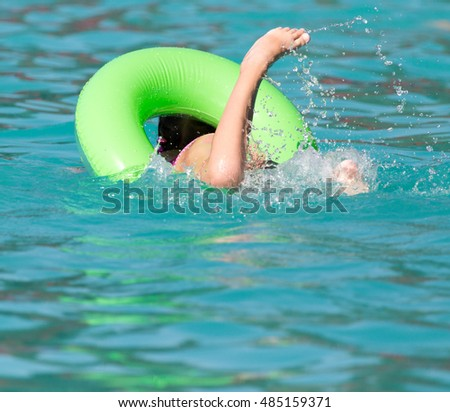 girl with a green balloon in the pool