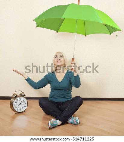 Girl with a green umbrella sits on the floor next to big clock