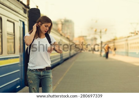 Girl with a guitar at train station. Retro toned image - stock photo