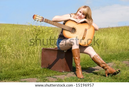 girl with a guitar sitting on the suitcase outdoor