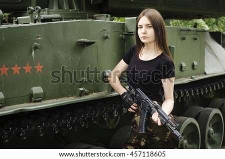 Girl with a gun near the armored vehicles - stock photo