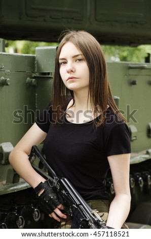 Girl with a gun, posing near the armored vehicle - stock photo
