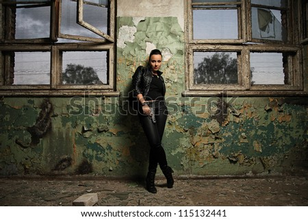 girl with a gun standing against the wall - stock photo